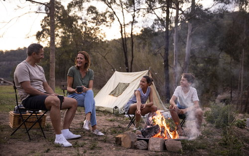 family outside tent with fire
